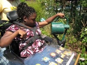 Une jeune élève arrose dans le jardin de la Melvin Sharpe Health School.