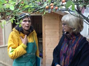Anne et Suzanne devant la cabane de jardin où sont entreposés bottes, outils, brouette, etc...