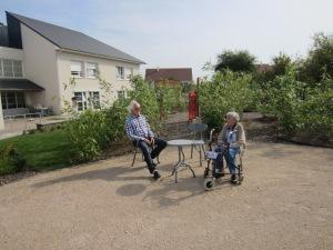 Place centrale avec Michel Racine parlant à une pensionnaire. En arrière plan, porte rouge symbolisant le passage On ne l'empreinte pas, on passe à côté.